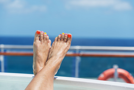 feet in water: female feet on board a cruise ship - the concept of a cruise vacation