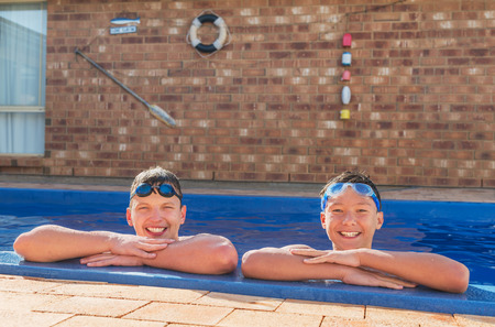 inground: Two young swimmers happy in their private inground pool