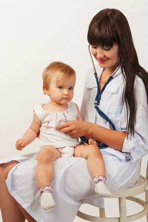 pediatrist: Pediatrician woman doctor with baby girl patient on light background