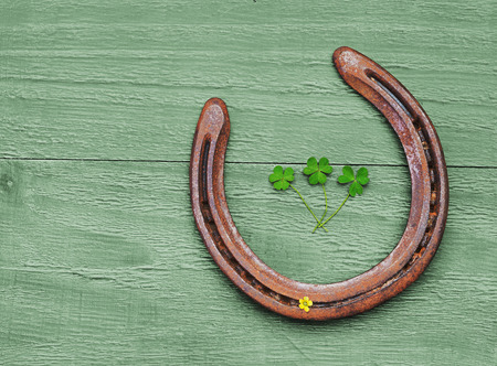 Old horseshoe and clover leaves on vintage wooden background photo