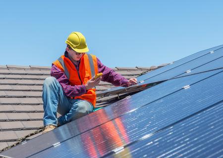 paneles solares: trabajador joven que controla los paneles solares en tejado de la casa Foto de archivo