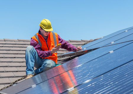 energy grid: young worker checking solar panels on house roof