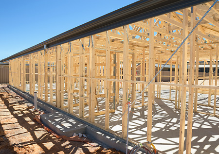 site preparation: New residential construction home framing against a blue sky