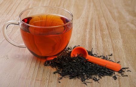 loose leaf: cup of tea and  pile of loose leaf tea on vintage wooden table