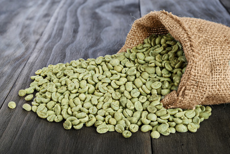coffee sack: burlap sack of green coffee beans on old wooden table