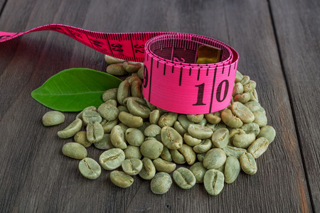 Green coffee beans with leaf and  measuring tape on vintage dark wooden surface.Concept of weight loss