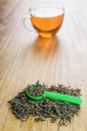 loose leaf: Pile of loose leaf green tea with spoon on vintage wooden table