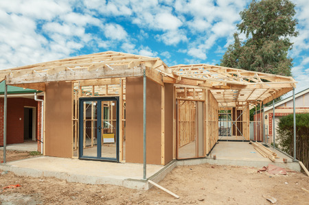 residential home: New residential construction home wooden framing against a blue sky Stock Photo