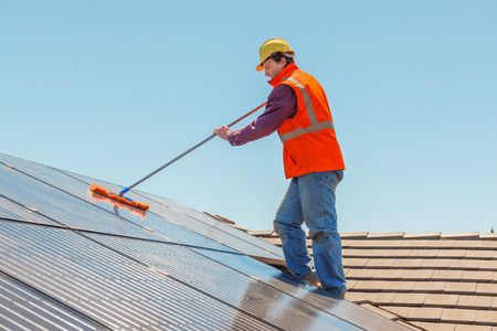 Young worker cleaning solar panels on the roof.Focus on the worker. Stock Photo