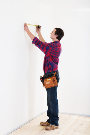 Young worker handyman with measuring tape near the wall in room photo