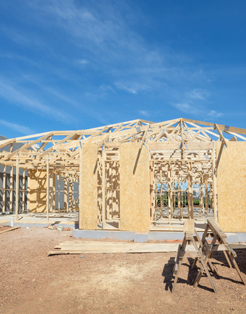 construction materials: New residential construction home framing against a blue sky.