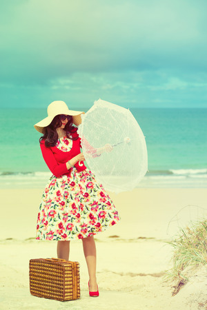 yellow dress: beautiful lady in red with umbrella near the sea in retro style Stock Photo