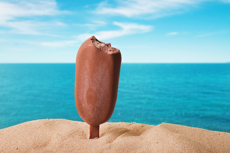 ice: classic chocolate ice cream with drops on the beach background