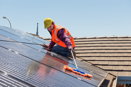 Young worker cleaning solar panels on the roof.Focus on the worker. Banque d'images