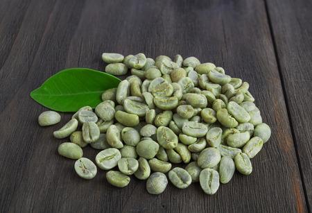 ejotes: Granos de café verde con la hoja sobre la superficie de madera oscura de la vendimia