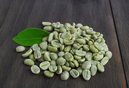 Green coffee beans with leaf  on vintage dark wooden surface Banque d'images