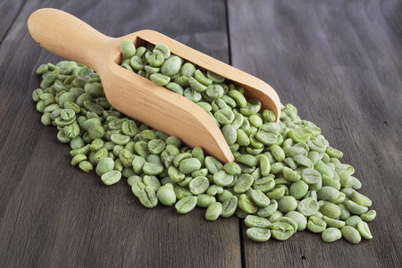 Green coffee beans in wooden scoop on vintage wooden surface