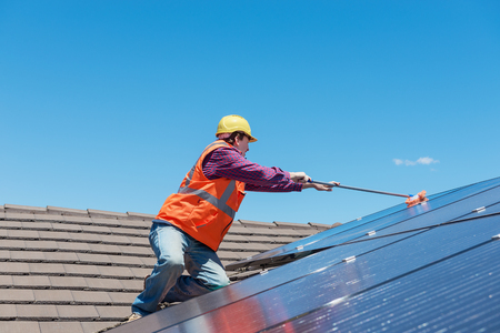 young worker cleaning solar panels on house roof Standard-Bild