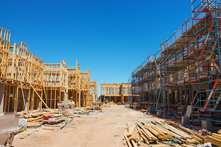materiales de construccion: Construction site with the house in scaffolding against a blue sky