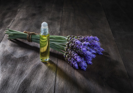 fresh lavender flowers and essential oil as natural aromatherapy for headache and migraine relief on old wooden background Stock Photo