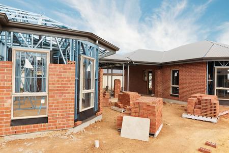 青空の金属フレーミングとレンガの家住宅新築