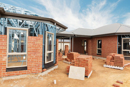 ladrillo: Casa de nueva construcción residencial de ladrillo con estructura metálica contra un cielo azul