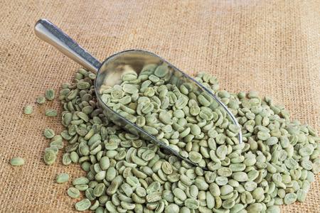 ejotes: Granos de café verde en cuchara de metal en la superficie de arpillera Foto de archivo