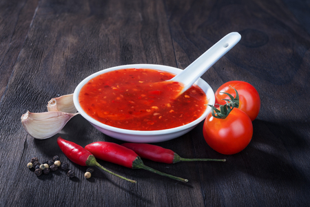 aroma bowl: red hot sweet chilli sauce over old wooden background Stock Photo