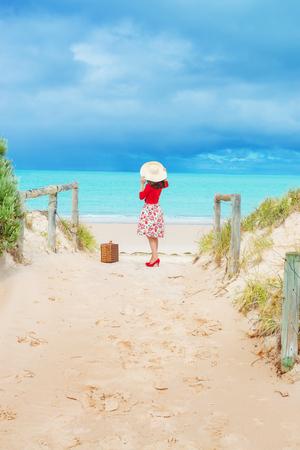 mujer con maleta: hermosa viajero de mujer en vestido de estilo retro en la playa y las dunas