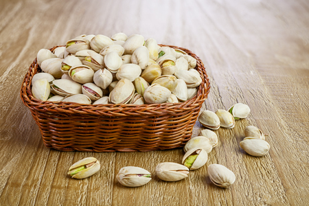 wooden basket: Pistachios nuts  in wicker basket on vintage wooden table