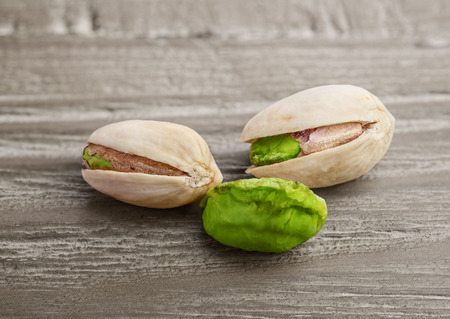 pistachios: Pistachio nuts  on a vintage wooden background