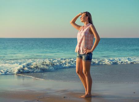 femme romantique: Belle fille sur la plage d'été face à la mer, à la lumière du soir