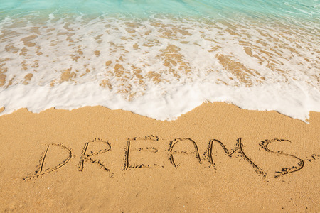 Dreams message on the beach sand - vacation and travel concept