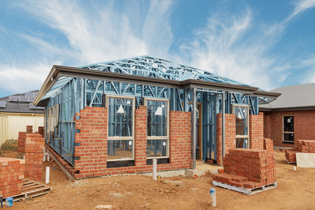roof framing: New residential construction home from brick with metal framing against a blue sky Stock Photo