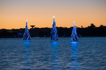 holiday tradition: Christmas trees in the sea water with illumination at sunset Stock Photo