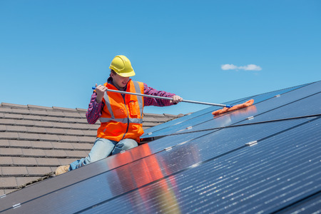 young worker cleaning solar panels on house roof Stock Photo