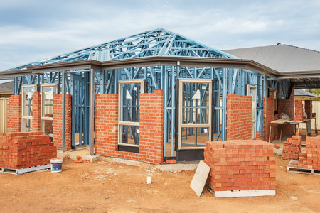 new construction: New residential construction home from brick with metal framing against a blue sky Stock Photo