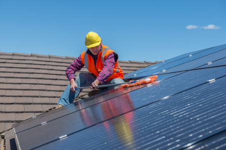 Young worker cleaning solar panels on the roof.Focus on the worker. Standard-Bild