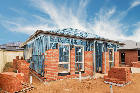 framing: New residential construction brick home with metal framing against a blue sky