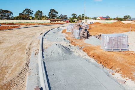 housing lot: new sidewalk during construction and new plots for homes construction Stock Photo