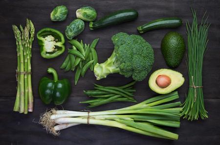 黒い木製ヴィンテージ テーブルの上の新鮮な緑の有機野菜。トップ ビュー 写真素材