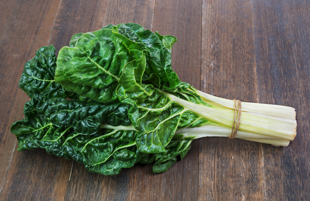 silverbeet hojas verdes frescas de verduras en el fondo de madera vieja