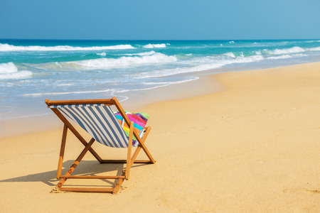 deckchair: Deckchair with colorful bag on the beach near blue water side - vacation and travel concept.Striped deck chair on the sand. Stock Photo