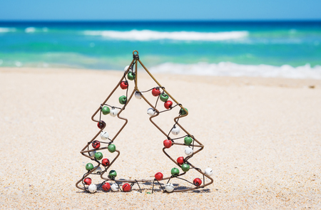 small metal christmas tree with jingle bells on the beach new year and christmas holiday - Small Metal Christmas Tree