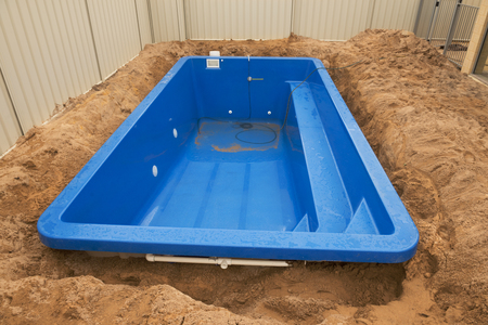 Installation plastic fiberglass pool in the ground at house backyard. Construction site Stock Photo