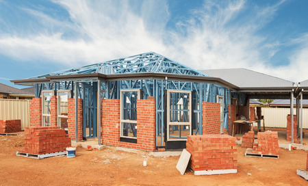 New residential construction home from brick with metal framing against a blue sky Archivio Fotografico