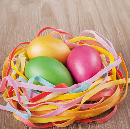 painted wood: multicolored easter eggs  in the nest on old wooden table Stock Photo