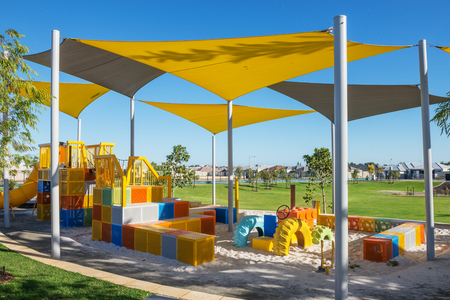 suburban outdoor colorful playground with green grass lawn on background in the morning Standard-Bild