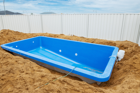 Swimming pool under construction.Installation plastic fiberglass pool in the ground at house backyard. Construction site Stock Photo