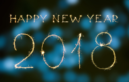 Happy new year and digits 2018 written with sparklers and bokeh isolated on black Stock Photo